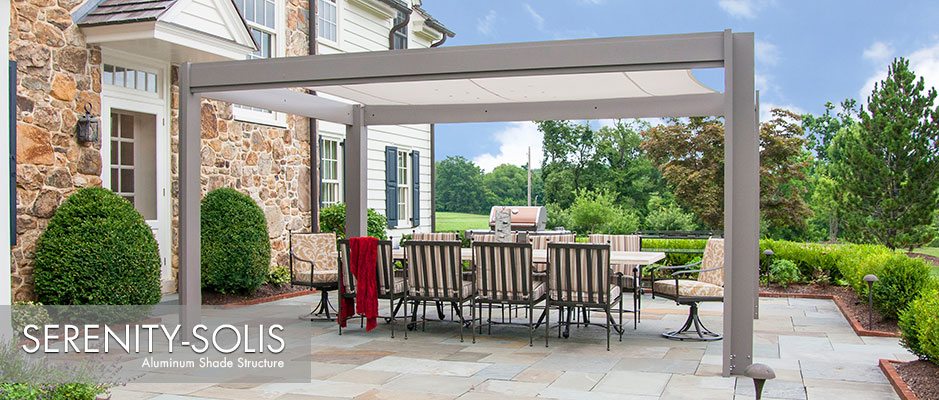 Aluminum shade structure with fabric canopy over stone patio next to traditional stone house