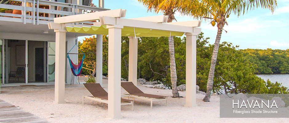 Tan colored Havana fiberglass pergola kit with green fabric canopy on sandy beach by lagoon