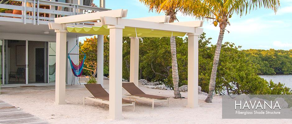 Tan colored Havana fiberglass pergola kit with green fabric canopy on sandy beach by lagoon